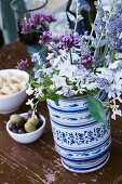 Garden flowers in painted ceramic vase on wooden table