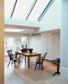 Dining area in open-plan living space in converted loft with large skylights