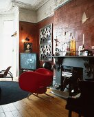 Red designer armchair in front of fireplace containing stereo in luxurious Baroque-style living room
