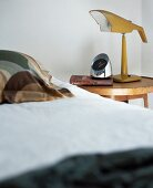Detail of bedroom with bedside lamp and alarm clock on bedside table
