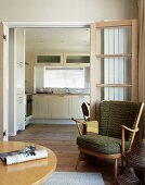 50s-style armchair in front of open double door with view of modern kitchen