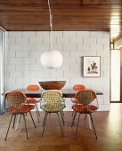 Dining area with wire mesh chairs in dining room with sand-lime brick wall