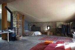 Schlafplatz in offenem Dachraum mit Natursteinwänden