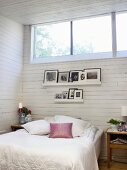 White bedroom with framed photos above bed