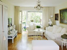 Comfortable sofa and armchair with valance in classic, white living room with large window and balcony door