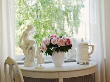 Bouquet of peonies between figurines and beer stein on white, semi-circular console table below window