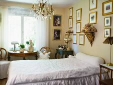 Simple single bed in bedroom with pictures on wall and antique wooden furniture