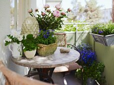 Mosaic table and wicker chairs on balcony lavishly decorated with flowering plants in various containers