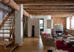 Open-plan living room with rustic wood-beamed ceiling and foot of staircase