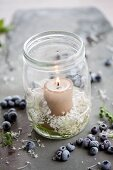 Candle in preserving jar with scabious, bilberries