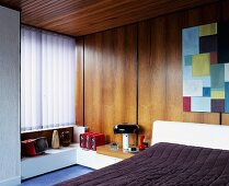 Wood-panelled, fifties-style bedroom with vertical blinds at window