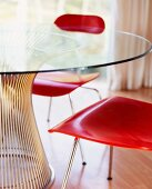 Wooden, red-stained chairs at glass table with metal foot