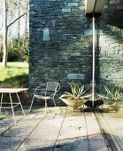 Sunny terrace corner with stone wall and metal furniture on old stone slabs