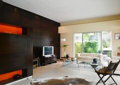 Modern living room with dark wooden wall, animal skin rug and acrylic glass coffee tables