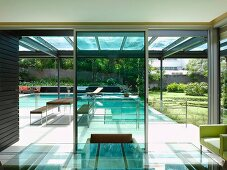 View from dining room with glass table to roofed terrace with swimming pool