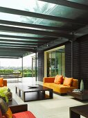 Modern colonial style seating in dark, African wood on glass-roofed terrace with vista