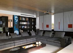 Grey sofas with separate back cushions and designer coffee table in living room with projector on concrete ceiling and sliding curtains