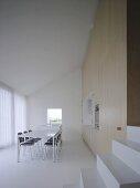 Stufen zu modernem Sitzungsraum mit in Schrankwand integrierter Teeküche