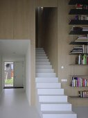 Treppenaufgang mit weissen Blockstufen neben Blick in Flur mit Fensterelement an Eingangstür