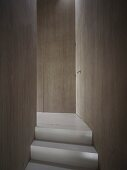 Oberste Treppenstufe in puristischem Flur mit flächenbündig in Holzverkleidung integrierten Türen