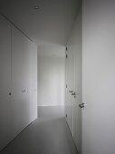 Gangflucht mit glatten Einbauschränken und Edelstahlgriffe an in Wandverkleidung integrierten Türen