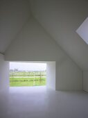 Empty, modern attic room with frameless, glazed wall aperture and view of landscape