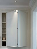 Glasses in fitted cupboard with modern folding door in traditional room with stucco ceiling