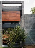 House with concrete facade and wooden shades in front of windows