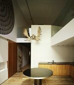 Gallery and open-plan kitchen with round table & antlers