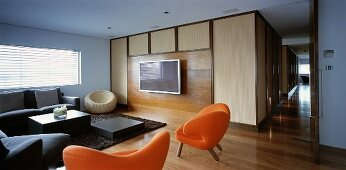 Living room with sofa, orange armchairs & TV