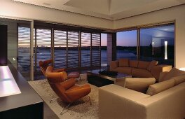 Living room with sofa, armchairs, coffee table & sliding louver doors leading to terrace