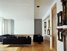 Black sofas and collection of antique picture frames in modern living space
