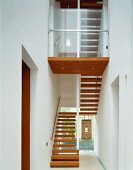 Modern, white stairwell with wooden stair treads