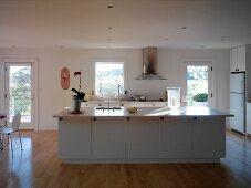 White, free-standing island in open-plan kitchen