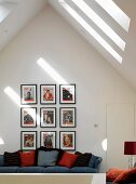 Collection of pictures above sofa with scatter cushions in attic storey with skylights