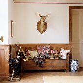 Foyer with rustic wooden bench and hunting trophy on wall