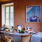 Laid dining table with gingham table cloth in front of wall painted light dusky pink