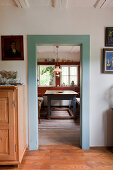 Doorway with wooden frame painted pale blue and view into rustic dining room beyond