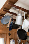 Vintage cooking equipment and a tin milk churn hanging from a wooden frame under the ceiling