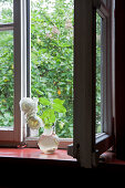 White roses in glass jug in front of open window with view of garden