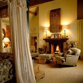 Corner of a canopied bed in front of upholstered armchairs around open fire