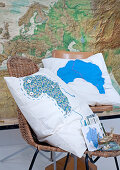 Cushions with cartographic motifs on chairs in front of large map
