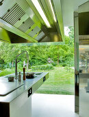 Stainless steel designer hob with extractor hood in front of glass wall of house with garden