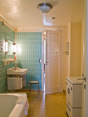 Original 50s bathroom with tiles in baby blue and yellow, steel tube stool and vintage washing machine