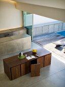 Blick von oben auf Designer Esstisch mit Stühlen in kubischer Form und monolithischem Küchenblock vor offener Terrassenschiebetür mit Holzdeck und Pool