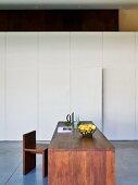 Esstisch und Stuhl aus dunklem Holz vor weissem Einbauschrank
