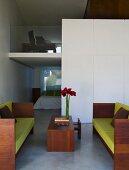 Sofa mit lindgrünen Polstern und Holzrahmengestell mit passendem Couchtisch in modernem Wohnraum mit Blick auf Galerie und in offenen Schlafraum