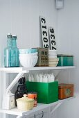 Crockery, swing-top bottles, candles, number plates and tins on white, wall-mounted shelves