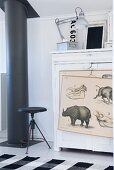 Black stove pipe and vintage stool next to white cabinet with drawings hanging on front