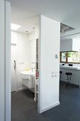 View into bathroom with white fittings and dark slate floor